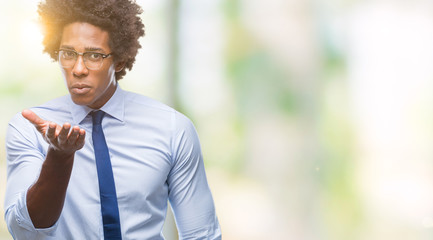 Afro american business man wearing glasses over isolated background looking at the camera blowing a kiss with hand on air being lovely and sexy. Love expression.
