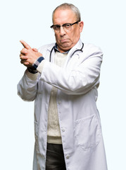 Handsome senior doctor man wearing medical coat Holding symbolic gun with hand gesture, playing killing shooting weapons, angry face