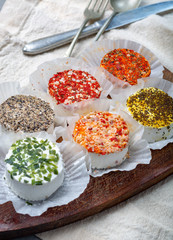 Assortment of French fresh white soft goat cheeses with different tastes topping made with herbs, paprika, indian curry, bruscetta, chives and dried tomatoes
