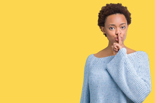 Young beautiful african american woman wearing a sweater over isolated background asking to be quiet with finger on lips. Silence and secret concept.