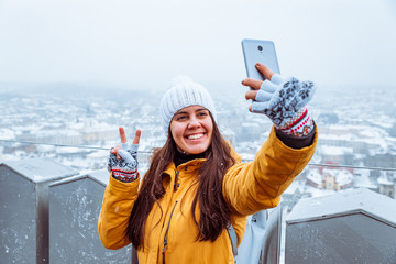 young pretty adult woman taking selfie with beautiful view of old european city