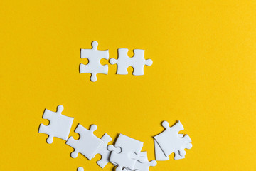 Jigsaw puzzles placed on a yellow background Creative concept with copy space