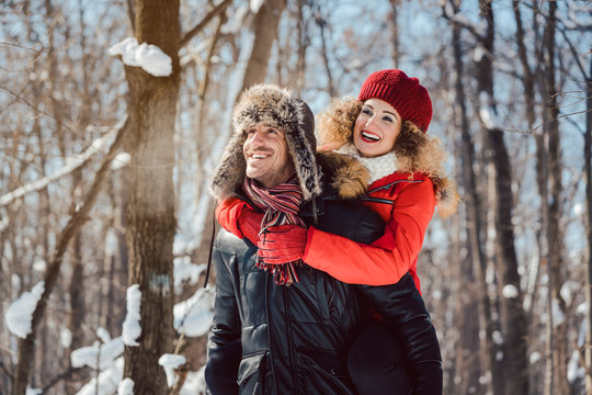 Man carrying his woman piggyback on a winter day in a joyful manner, they have fun in this season