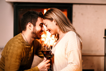 Happy couple smiling and kissing while having a drink by the fireplace. Lovely people lifestyle