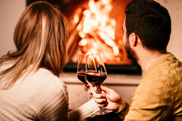 Chill couple having wine drinks and looking at fire burning in fireplace, in cosy living room