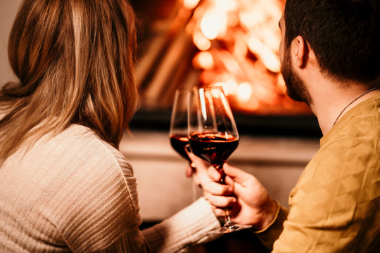 In love people having a glass of wine by the fireplace and enjoying a lovely evening at home
