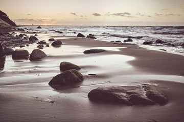Scenic beach with a stones at sunset, selective focus, color toning applied.