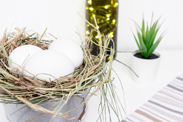 Easter white chicken eggs in straw nest, green spring plants and easter holiday decoration on white background and country style beige striped cloth