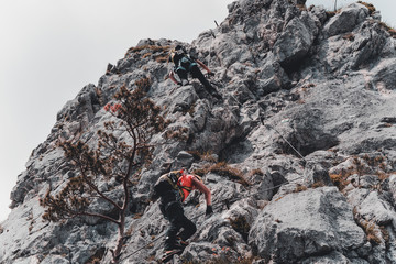 Image of young man mountaineer climbing on a rock in the mountains