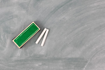 Back to school concept with green chalkboard plus eraser and chalk