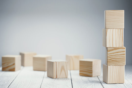 Tower of four wooden cubes on neutral background with copy space