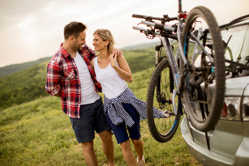 Loving couple stnding next to the car with bicycles