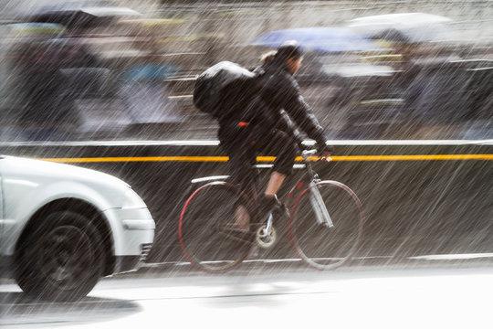 cyclist on a city street at heavy rain