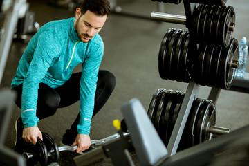 Handsome young man preparing dumbbells in gym