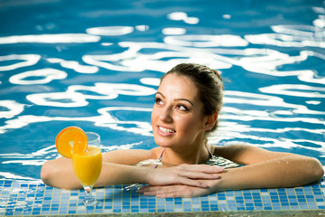 Attractive smiling brunette woman in swimming pool with cocktail