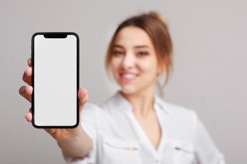 Happy woman showing blank smartphone screenover background