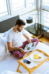 Young man having breakfast in bed and reading magazine in the room
