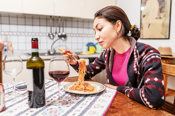 Asian woman eating spaghetti and drinking wine in the kitchen at home