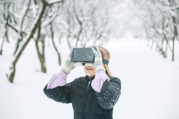 girl in glasses of virtual reality in the winter snow-covered forest.