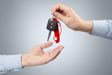 Two hands, giving and taking a car key on gray background