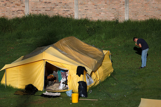 Venezuelan migrant brushes his teeth outside a tent in a temporary humanitarian camp that is closed by the government in Bogota