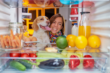Woman and her dog in front of fridge late at night. Picture taken from the inside of frigde.