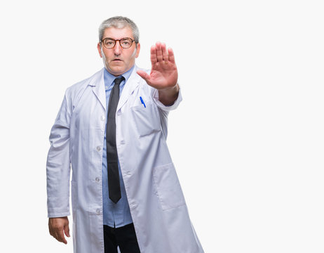 Handsome senior doctor, scientist professional man wearing white coat over isolated background doing stop sing with palm of the hand. Warning expression with negative and serious gesture on the face.