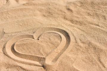 Hand drawn heart on sea sand on the beach