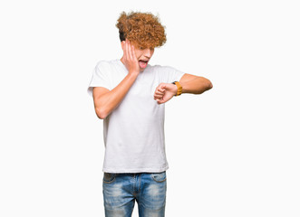 Young handsome man with afro hair wearing casual white t-shirt Looking at the watch time worried, afraid of getting late