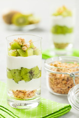Healthy yogurt dessert with granola and fresh cut kiwi in tall glasses with ingredients.