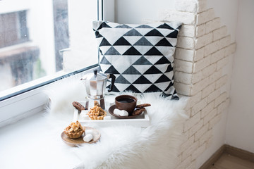 Cozy winter home arrangement on windowsill, coffee and cookies o