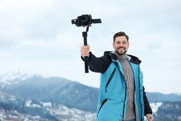 Man with stabilizer and camera recording video in mountains. Winter vacation