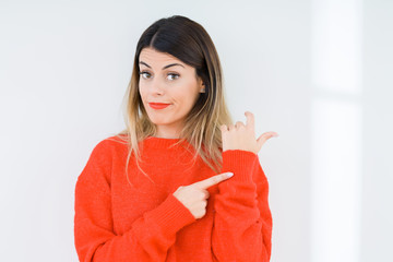 Young woman wearing casual red sweater over isolated background In hurry pointing to watch time, impatience, upset and angry for deadline delay