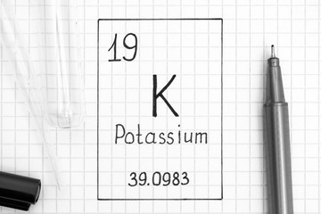 Handwriting chemical element Potassium K with black pen, test tube and pipette.
