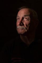 Dark portrait image of senior man, with copy space