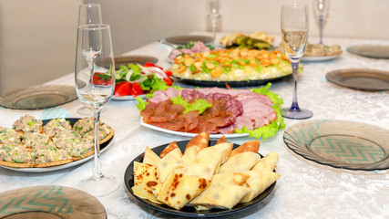 The festive table is served for the holiday of Carnival. Rolls of pancakes with sturgeon. Various dishes of Russian cuisine on the table
