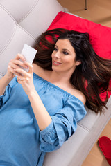 Top view photo of a beautiful smiling pregnant woman in an elegant blue dress while lying on a sofa and using her smartphone.