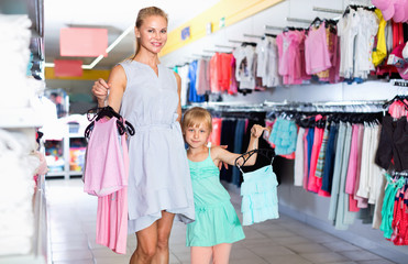 Female with girl choosing different clothes in the dress shop