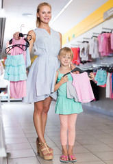 Portrait of young mom with girl choosing dress