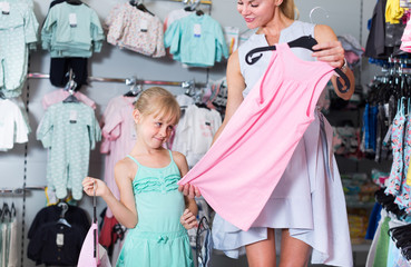 Daughter and mother are choosing clothes