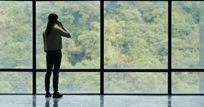Woman talk to cellphone over glass of window with green tree background