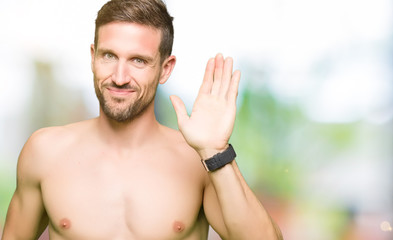 Handsome shirtless man showing nude chest Waiving saying hello happy and smiling, friendly welcome gesture