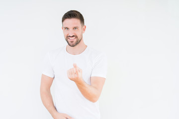 Young handsome man wearing casual white t-shirt over isolated background Beckoning come here gesture with hand inviting happy and smiling