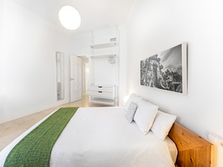 Clean bright bedroom with king size bed, duvet,side tables, lamps, photography. Minimalist white stylish interior
