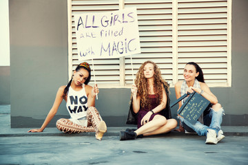 The girls are sitting on the street with a poster. International Womens Day. Women different nationalities,cultures and gender identity. Struggle for freedom, independence, equality