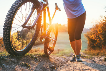 Cyclist man pushing a mountain bike up the hill close up image. Active travel on bicycle