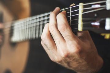 Plays acoustic guitar close-up