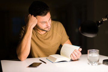 Young handsome man studying at home, reading a book at night