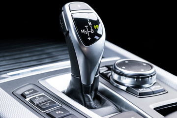 Automatic gear stick of a modern car. Modern car interior details. Close up view. Car detailing. Automatic transmission lever shift. Black leather interior with stitching.