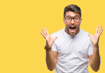 Young handsome man wearing glasses over isolated background celebrating crazy and amazed for success with arms raised and open eyes screaming excited. Winner concept Wall mural